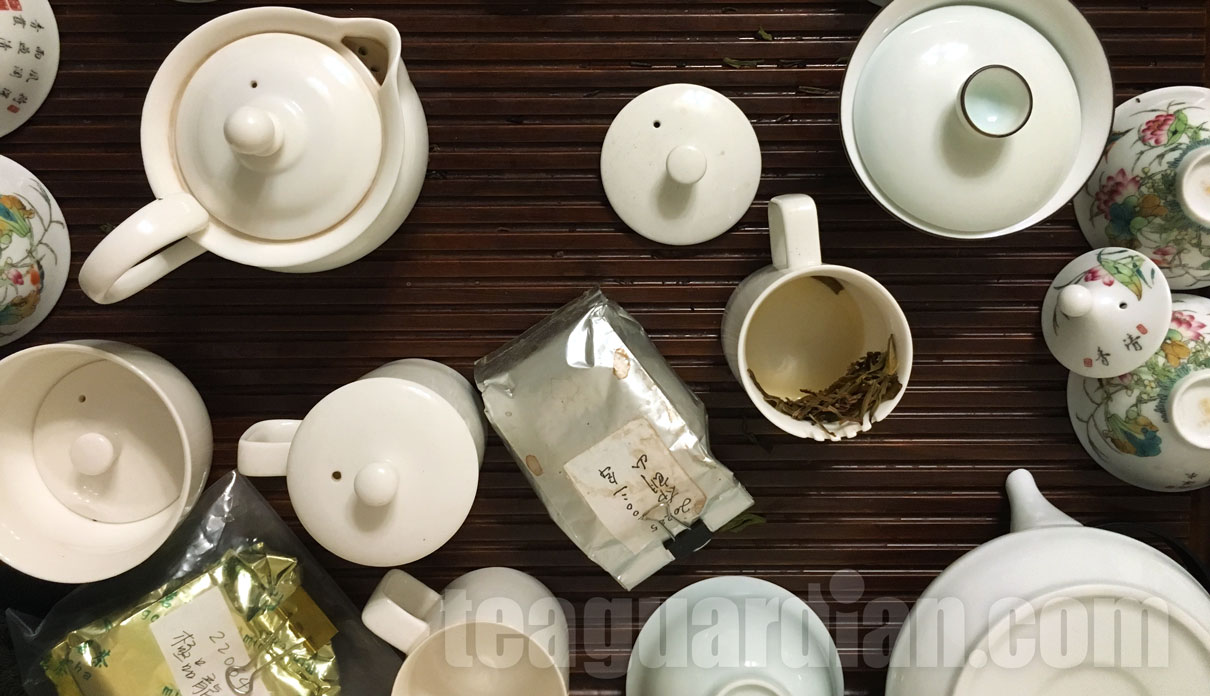 Tea tray scattered with cups, vessels and tea samples after a tea tasting session