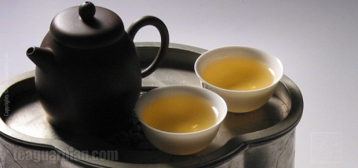 A small Yixing teapot with two porcelain gongfu teacups on a pew